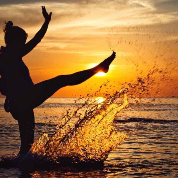woman splashing water in the sunset