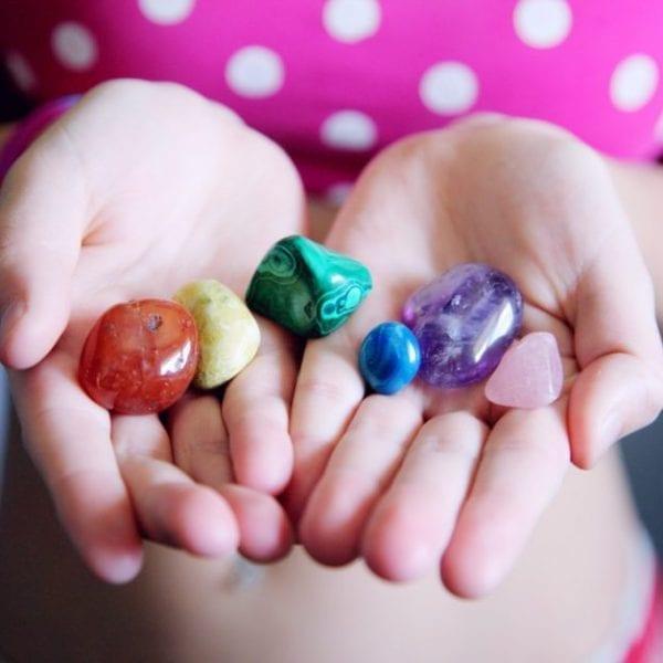 woman holding multicoloured gemstones