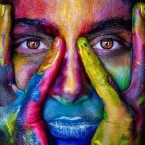 girl covered in colourful paint holding her face