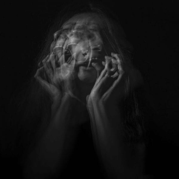 woman holding her face on black background