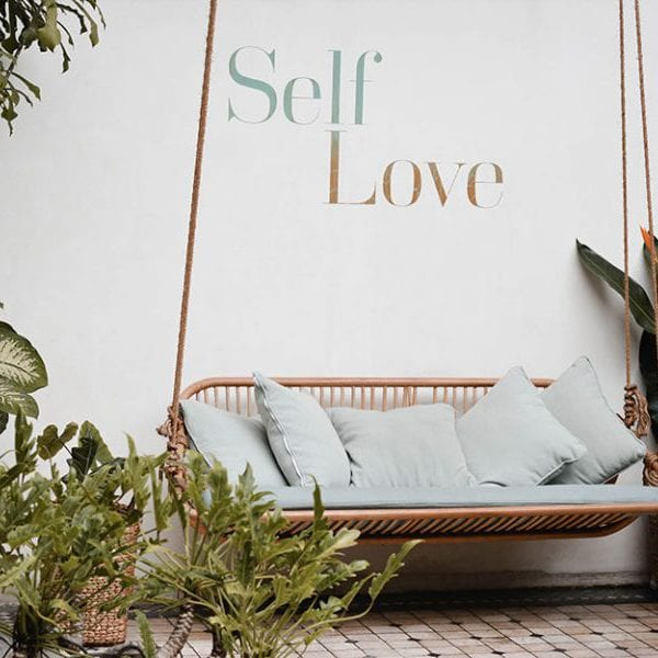 outdoor sofa wit self love written on the wall