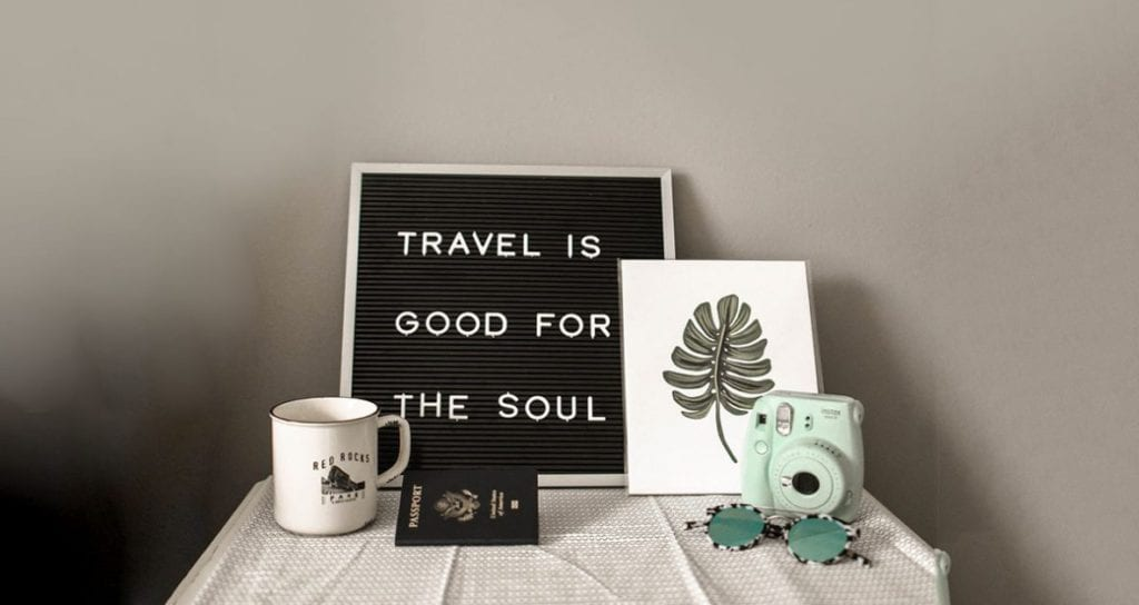 camera cop and sign saying traveling is good for the soul