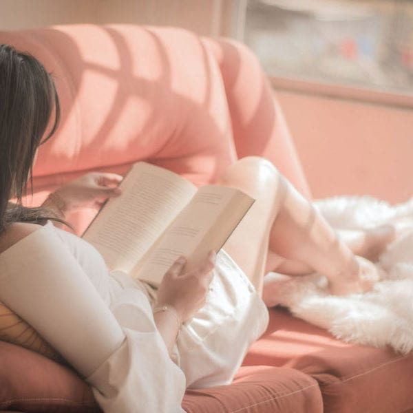 woman sitting in pink sofa reading a book