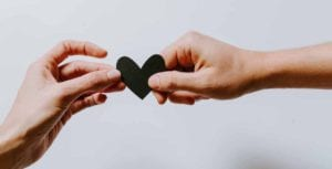 two hands holding a black heart