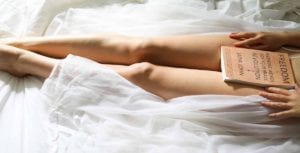 woman on white bed with book