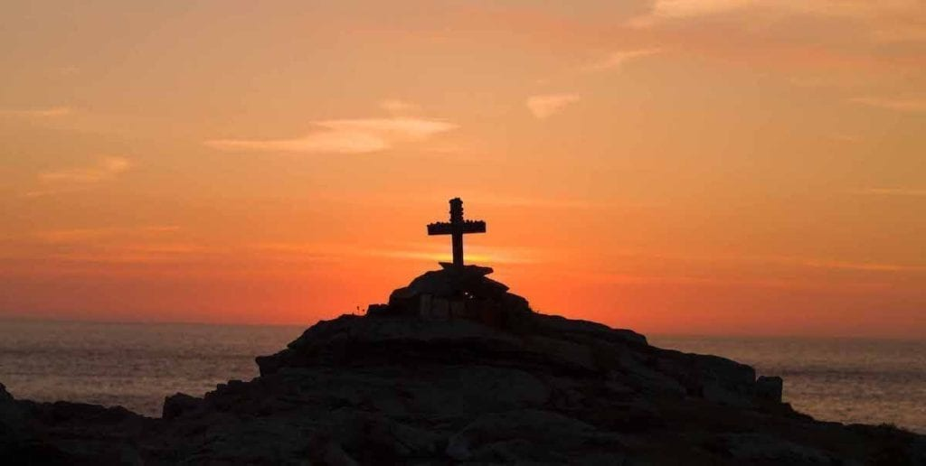 cross on a hill in sunset
