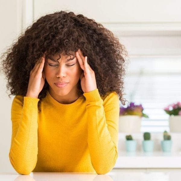 woman in yellow with a headache