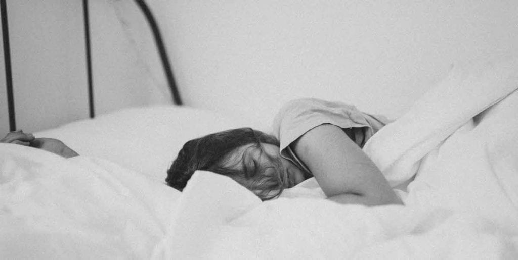 woman sleeping in white sheets