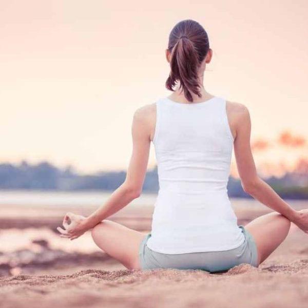 woman meditation on beach in sunset