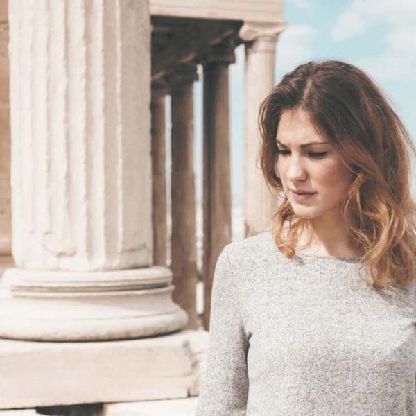 woman stood in front of ancient Greek building