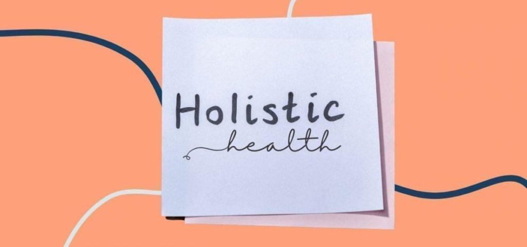 holistic health on post it note on orange background