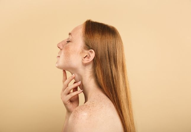 woman touching her chin and throath