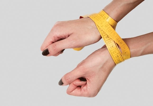 womans hand tied with measuring tape