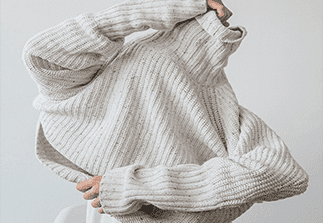 woman putting a white knitted jumper over her head